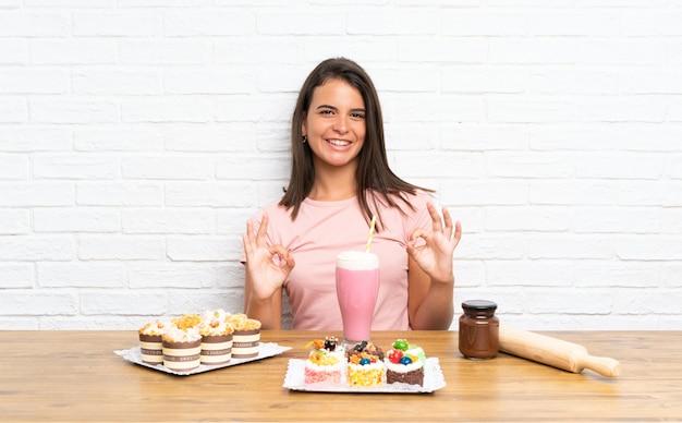 Ragazza con un sacco di diverse mini torte che mostrano un segno ok con le dita
