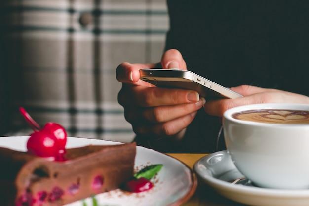 Ragazza con un telefono cellulare, caffè e torta in un caffè. mani femminili che tengono uno smartphone.