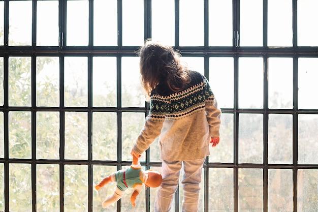Ragazza con una bambola guardando attraverso la finestra