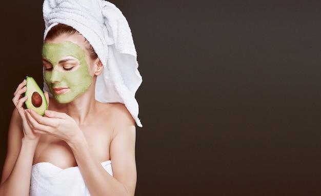 Ragazza con una maschera cosmetica di avocado. sfondo scuro, luce da studio.