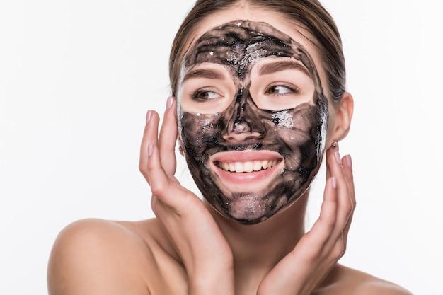Ragazza con una maschera cosmetica nera sul suo fronte che giudica una spazzola isolata su una parete bianca