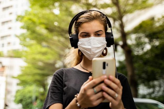 Ragazza con una maschera protettiva e le cuffie per ascoltare la musica usando il suo telefono cellulare in strada