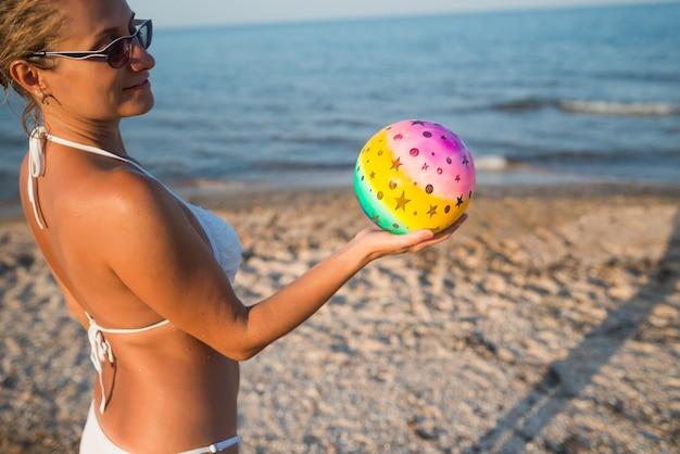 Ragazza con una palla vicino al mare.