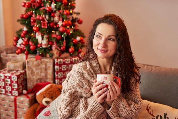 Ragazza con una tazza di marshmallow all'interno del nuovo anno a casa