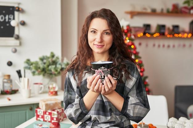 Ragazza con una tazza nella cucina di capodanno