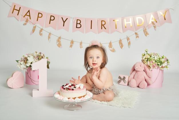 Ragazza con una torta di compleanno, sessione fotografica di un bambino di 1 anno