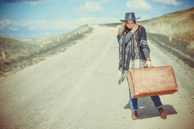 Ragazza con una valigia sulla strada