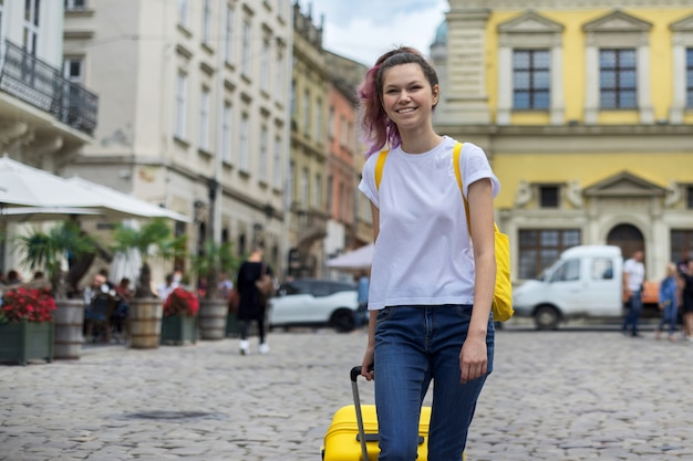 Ragazza con uno zaino e una valigia gialla sulla strada della città