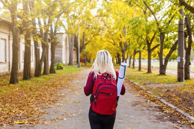 Ragazza con uno zaino nel parco di autunno