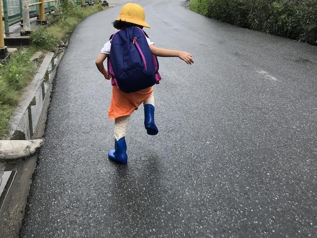 Ragazza con zaino sulla strada per la scuola.