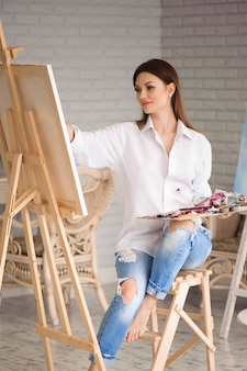 Ragazza concentrandosi su tela d'arte durante la pittura