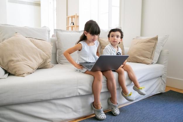 Ragazza concentrata e il suo fratellino seduto sul divano a casa, utilizzando il laptop per videochiamate, chat online, guardare video o film.