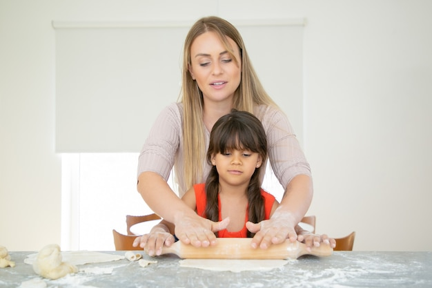 Ragazza concentrata e sua mamma che rotolano la pasta sul tavolo della cucina con la polvere di farina.