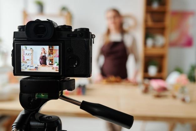 Ragazza contemporanea in mostra della telecamera di casa davanti al tavolo che registra una master class per la produzione di sapone