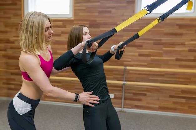 Ragazza d'aiuto dell'istruttore personale femminile di forma fisica per fare gli esercizi in palestra