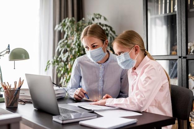 Ragazza d'aiuto della donna con i compiti mentre indossa una maschera medica