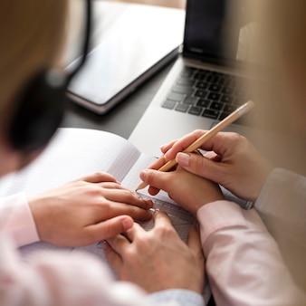 Ragazza d'aiuto della donna nel fare i suoi compiti