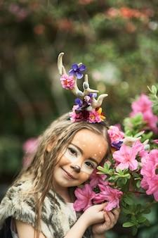 Ragazza da favola ritratto di una bambina in un vestito di cervo con una faccia dipinta nella foresta