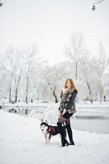 Ragazza dai capelli rossi che cammina al parco con il cane husky il giorno di inverno.