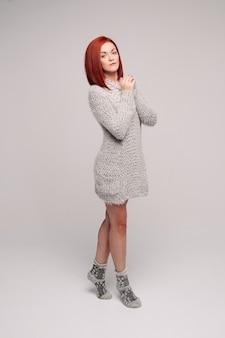 Ragazza dai capelli rossi che indossa un maglione grigio e calzini caldi.