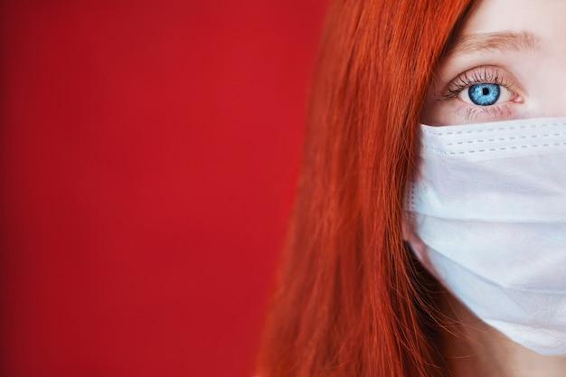 Ragazza dai capelli rossi con una mascherina medica su un copyspace rosso, donna dottoressa, donna con sguardo intenso, europeo, metà della sua faccia, capelli fluenti