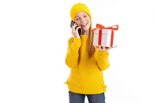 Ragazza dai capelli rossi europea che parla sul telefono con un regalo in sue mani su un bianco