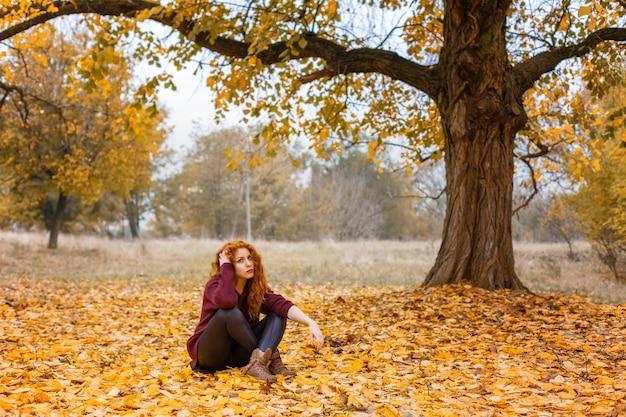Ragazza dai capelli rossi nella foresta di autunno che si siede sulle foglie gialle