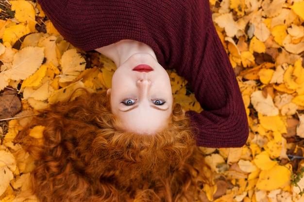 Ragazza dai capelli rossi sveglia che si trova sulle foglie gialle