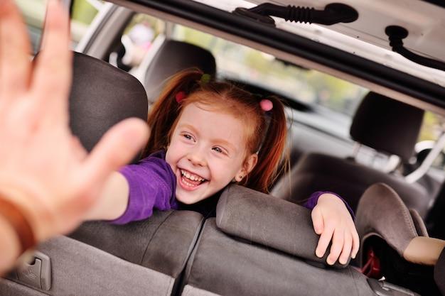 Ragazza dai capelli rossi sveglia che sorride nel salone dell'automobile