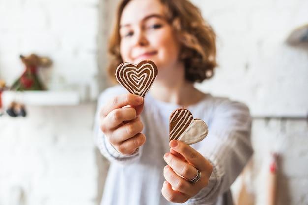 Ragazza dall'aspetto europeo che tiene i biscotti a forma di cuore, amanti, san valentino, cottura, cottura