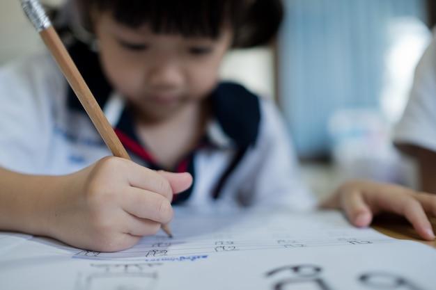 Ragazza dei bambini che fa i compiti con la madre, carta di scrittura del bambino, concetto di famiglia, tempo di apprendimento, studente, ritorno a scuola