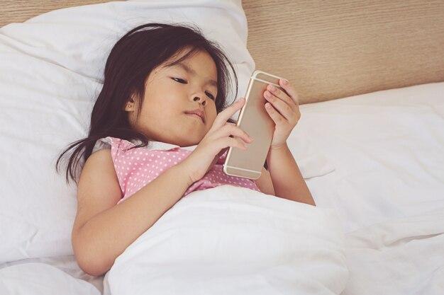 Ragazza dei bambini che manda un sms sullo smartphone e che si trova a letto a casa