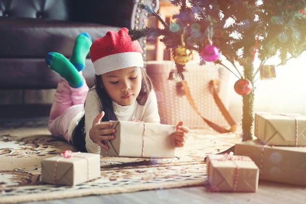 Ragazza dei bambini con disimballo confezione regalo in chistmas giorno
