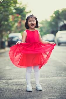 Ragazza dei bambini di asina che indossa emozione sorridente di felicità del fronte sorridente dentato del vestito rosso dalla gonna