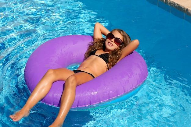 Ragazza dei bambini rilassata su anello piscina gonfiabile viola
