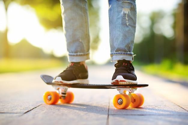 Ragazza dei pantaloni a vita bassa con lo skateboard all'aperto primo piano skateboard. donna sportiva attiva divertendosi nel parco