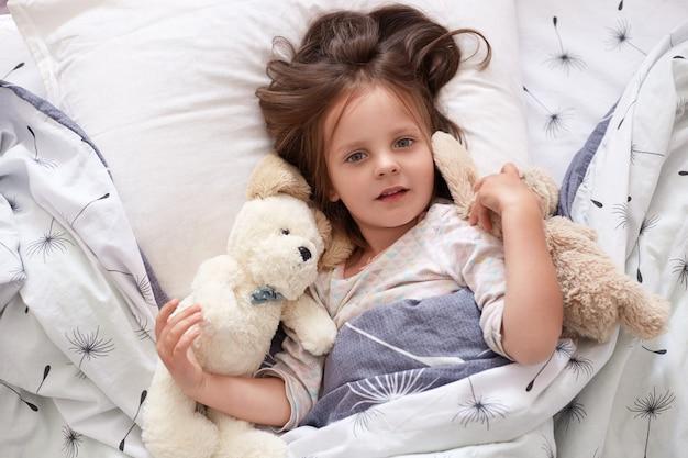 Ragazza del bambino a letto sdraiato con il suo orsacchiotto a casa, bambino elegante posa su lenzuola con dente di leone