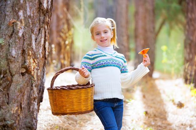 Ragazza del bambino alla ricerca di funghi finferli con cesto in autunno