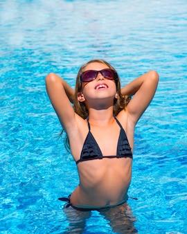 Ragazza del bambino bikini con occhiali da sole in piscina blu