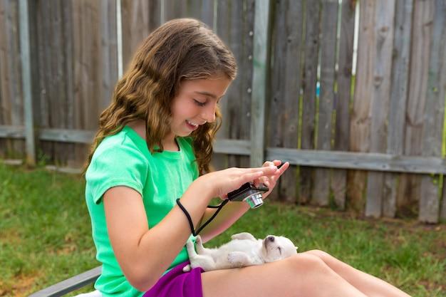 Ragazza del bambino che cattura le foto al cucciolo di cane con la macchina fotografica
