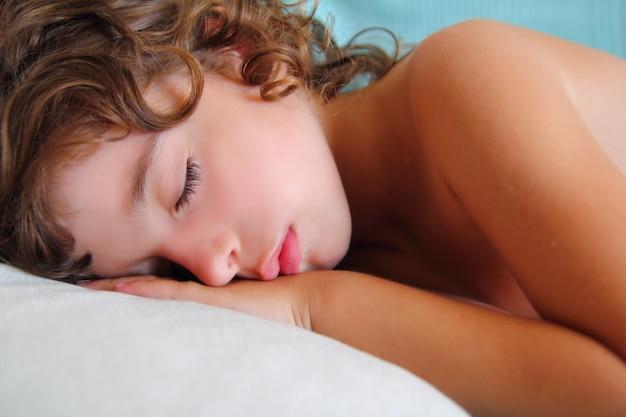 Ragazza del bambino che dorme sul cuscino in estate