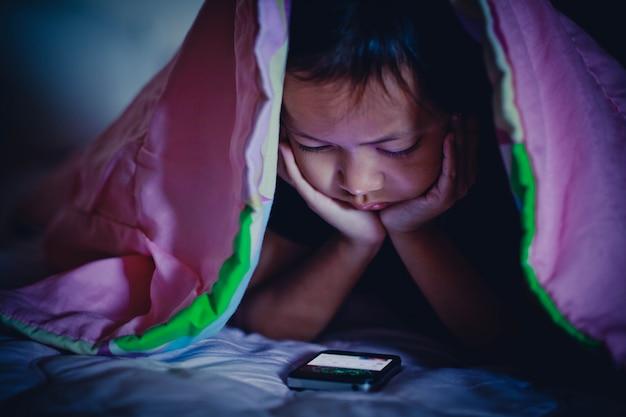 Ragazza del bambino che esamina smartphone nel buio sotto coperta