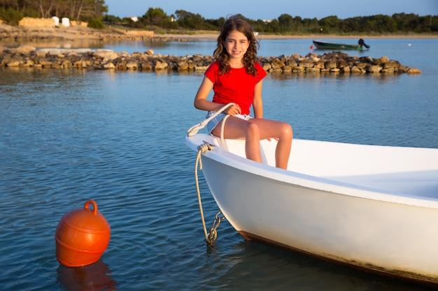 Ragazza del bambino che finge di essere marinaio in barca prua a formentera