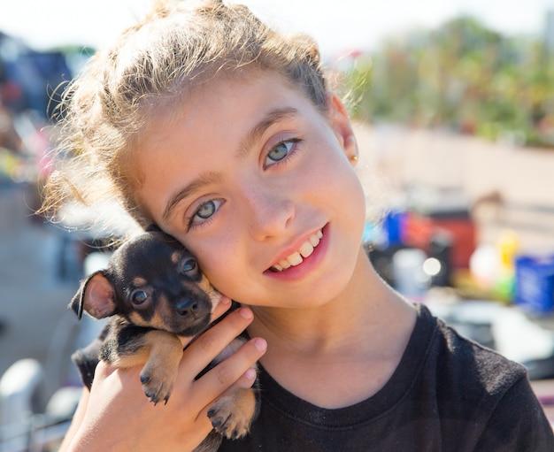 Ragazza del bambino che gioca con sorridere del cucciolo di cane