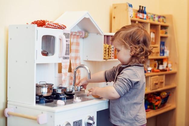 Ragazza del bambino che gioca la cucina del giocattolo