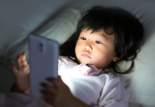 Ragazza del bambino che gioca smartphone sdraiato su un letto di notte