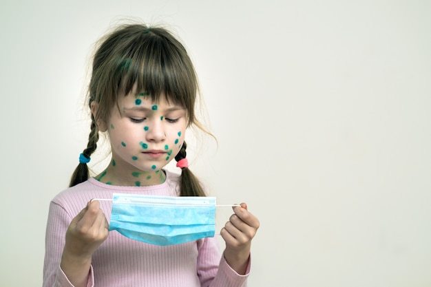 Ragazza del bambino che indossa blu maschera medica protettiva malata con varicella, morbillo o virus della rosolia con eruzioni cutanee sul corpo. protezione dei bambini durante l'epidemia di coronovirus. concetto di contagio covid-19.