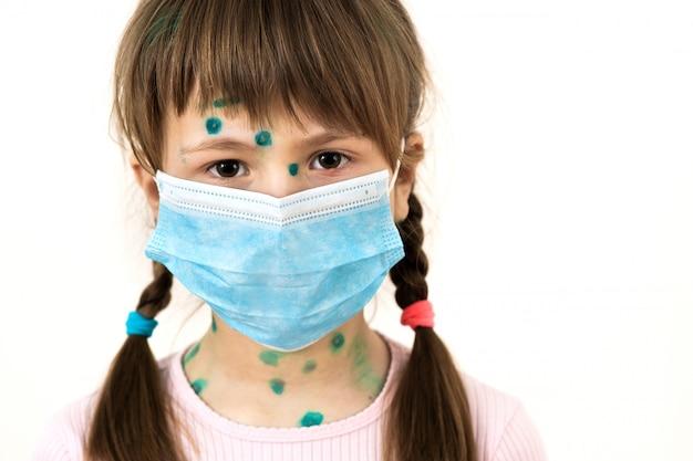 Ragazza del bambino che indossa maschera medica protettiva blu