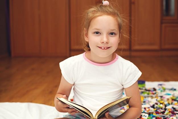 Ragazza del bambino che legge un libro a casa