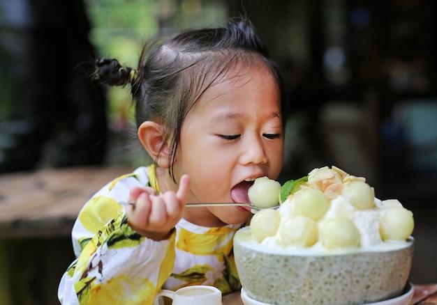 Ragazza del bambino che mangia il dessert coreano di bing su del melone